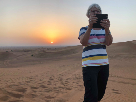 Decorative image showing a woman over 65 taking a selfy in-front of the sunset in the desert.